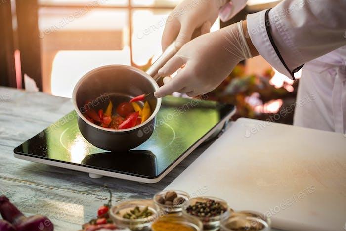 Hand in glove holding saucepan
