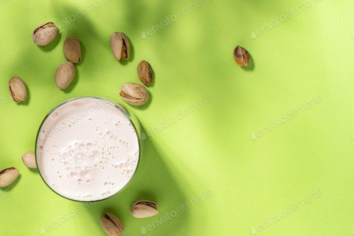 Vegan Pistachio nut milk in bottles, closeup, green background