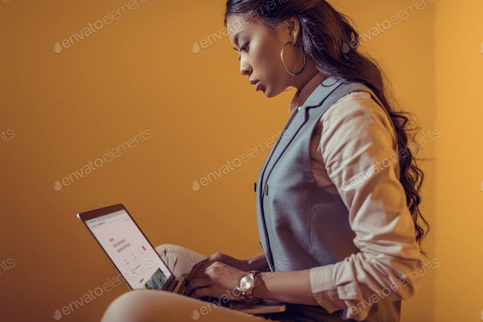 asian businesswoman using laptop with airbnb website in front of orange wall
