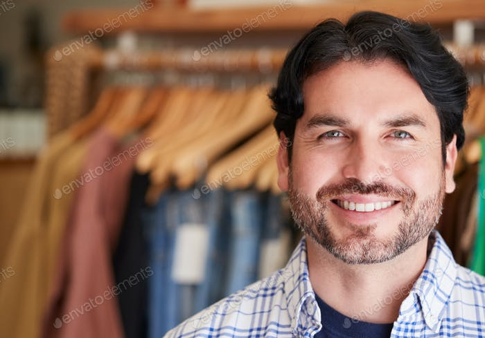 Portrait Of Smiling Male Owner Of Fashion Store Standing In Front Of Clothing On Rails