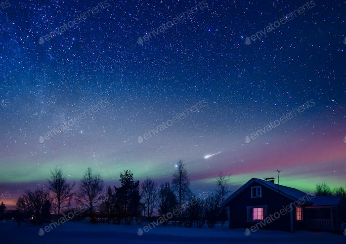 Cottage against the night sky with the Milky Way and the arctic Northern lights Aurora Borealis