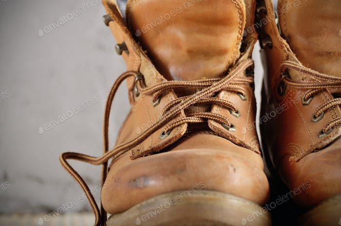 Yellow leather used work boots on concrete background closeup