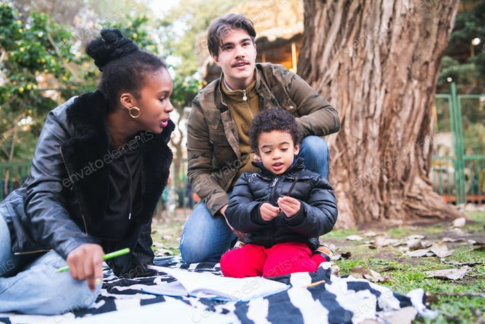 Mixed race ethnic family at park.