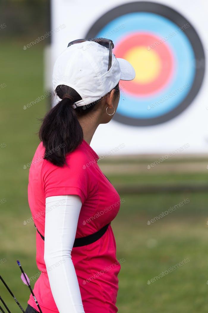 Atleta femenina practicando tiro con arco en el estadio