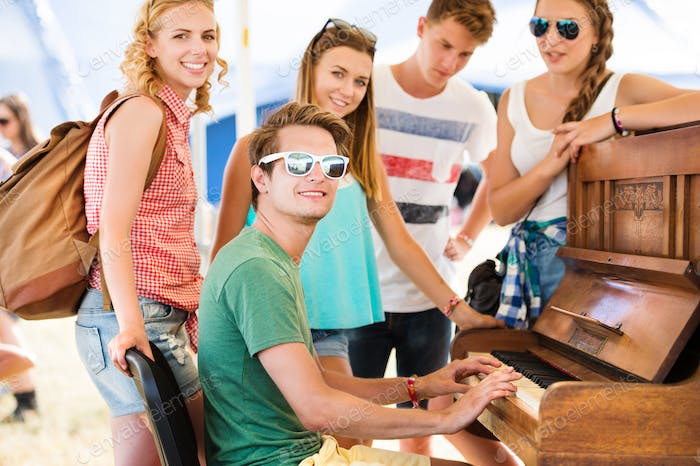 Teenagers at summer music festival, boy plays the piano