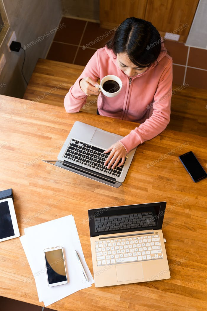Top view of woman drink of coffee when using the laptop computer
