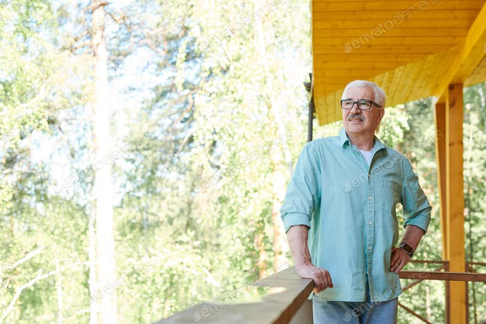 Happy mature retired man in casualwear relaxing in country house