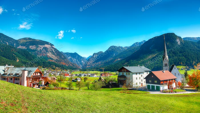 Alpine green fields and traditional wooden houses view of the Gosau village at autumn sunny day.