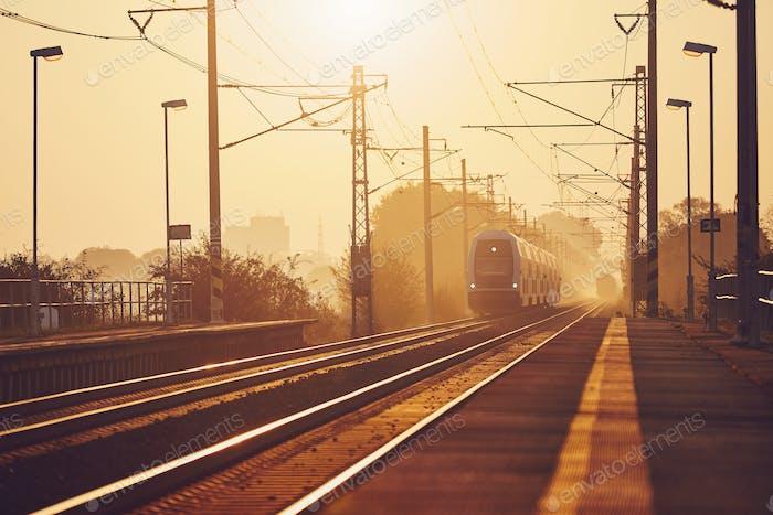 Personenzug bei Sonnenaufgang.
