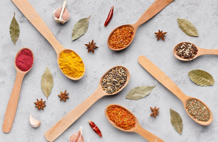 Spices and herbs on grey background, top view