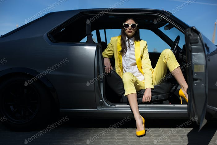 Stylish lady sitting in the car with door opened. Posh fashion girl driving sport car in a suit