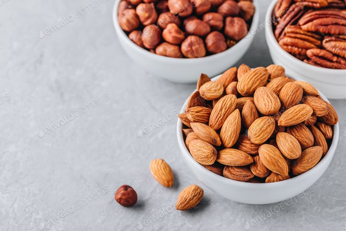 Almonds, pecans and hazelnuts in white bowls on grey background. Assortment of nuts.