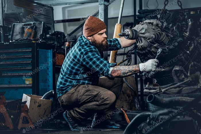 Mechanicl inspecting engine of a car in a garage.