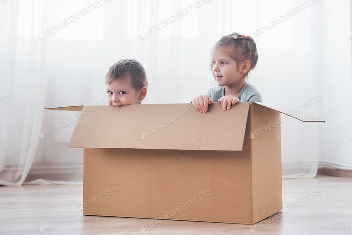 Two a little kids boy and girl just moved into a new home. Concept photo .. Children have fun.