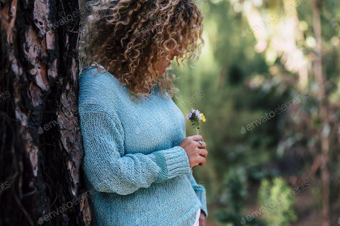 Die Natur genießen - Junge Frau pflegen ein wenig bunte frische Blume