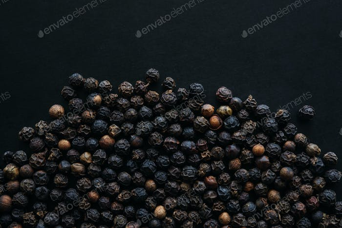 Close-up view of the black peppercorns on the black floor