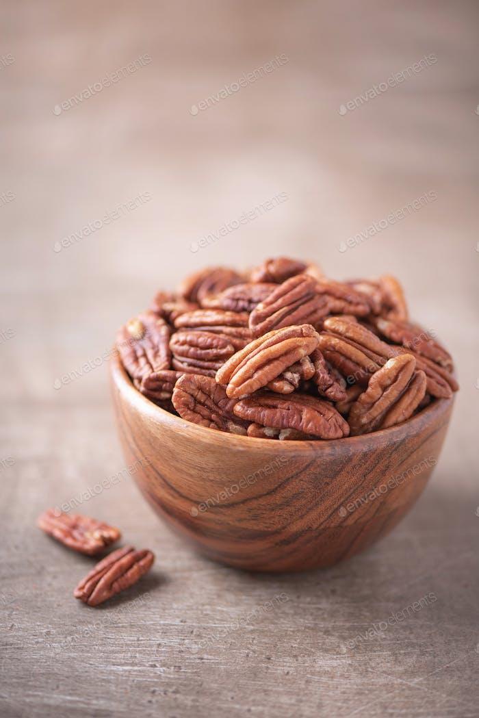Pecan nuts in wooden bowl on wood textured background. Copy space. Superfood, vegan, vegetarian food