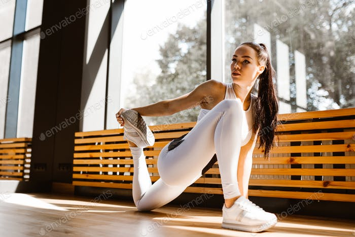 Slender dark-haired girl dressed in white sports clothes is doing stretching in front the mirror in