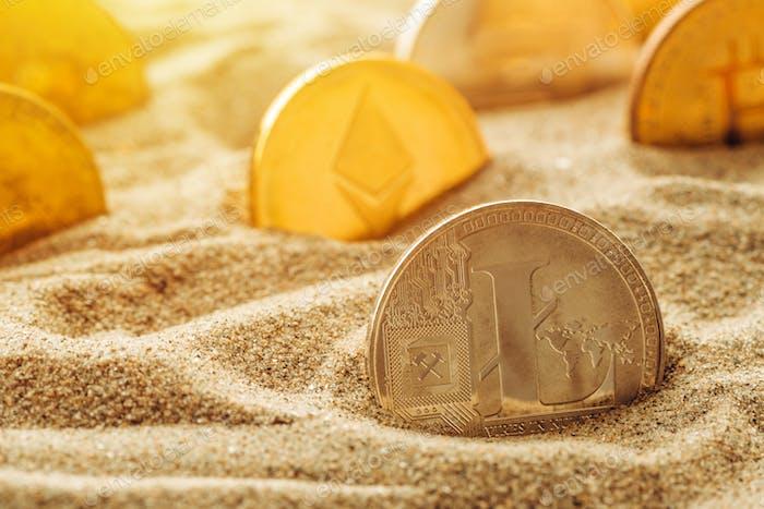 Silver Litecoin coin in sand