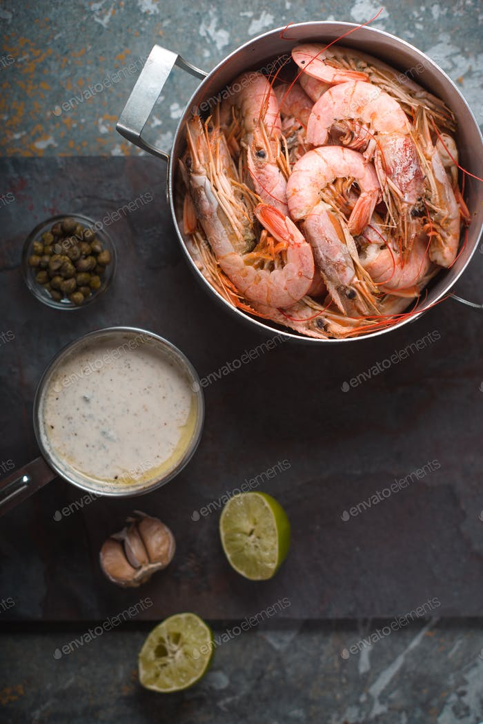 Prawns and savory sauce on the stone background