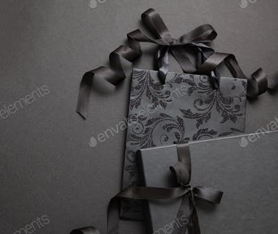 Black Friday sale concept. Black shopping bag and gift box on black background.