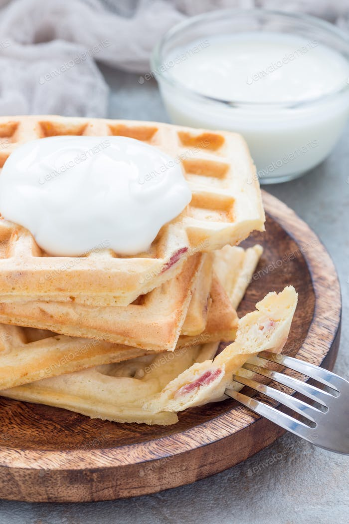 Homemade savory belgian waffles with bacon and shredded cheese, vertical