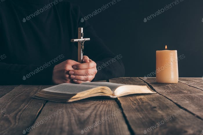 cropped image of christian sitting with cross in hands