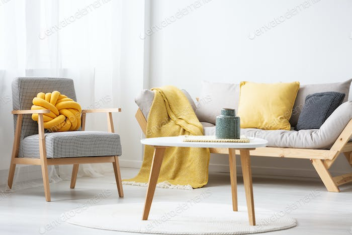 Patterned armchair next to settee with yellow blanket in flat in