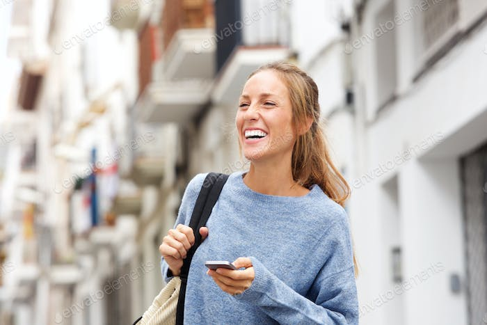 happy young woman in the city with mobile phone