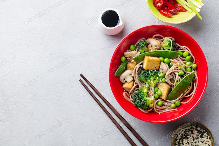 Soba Noodles with Vegetables and Fried Tofu in a Bowl. Grey Background. Top View.