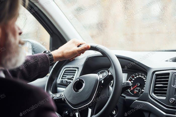 Модный старший мужчина в элегантной одежде находится в современном автомобиле