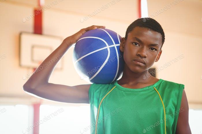 Portrait of confident teenage boy holding basketball