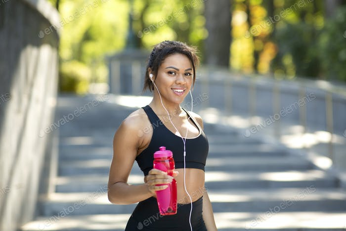 Attractive sporty black girl with bottle of water at park