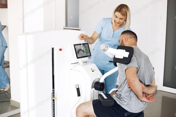 Patient trainiert mit Sportgeräten mit Therapeuten