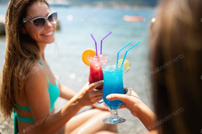 Beautiful girls drinking cocktails during summer vacation on beach