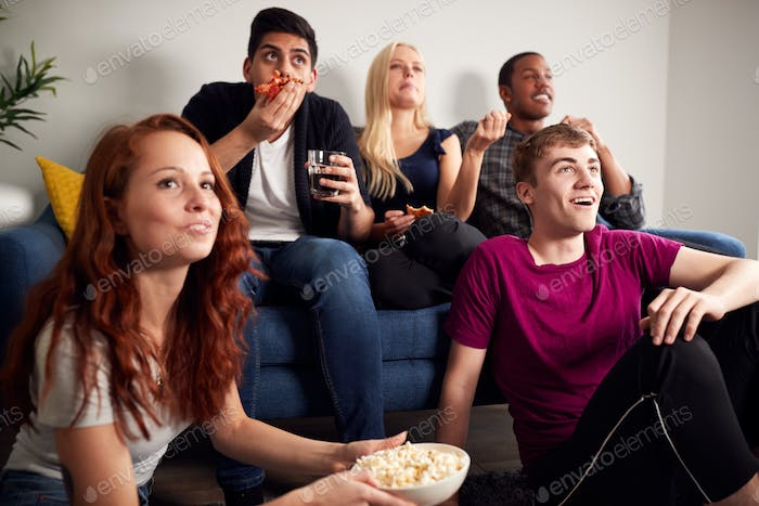 Group Of College Students In Shared House Watching TV And Eating Popcorn