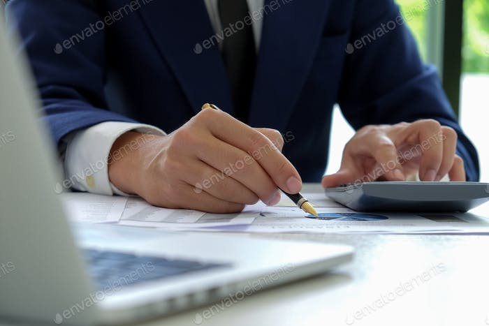 Businessman hand works on a calculator and uses a pen.