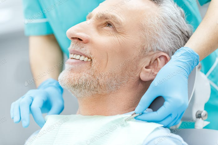 Cropped shot of smiling mature patient and dentist in medical gloves