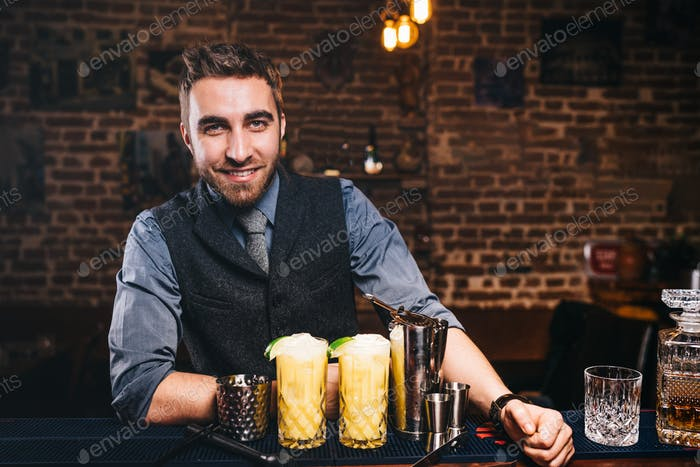 handsome barman smiling at camera, preparing cocktails and serving fresh drinks