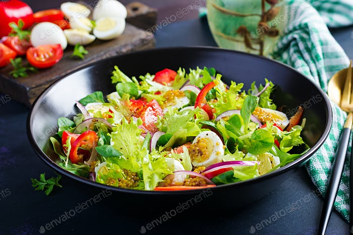 Fresh salad with vegetables tomatoes, red onions, lettuce and quail eggs.