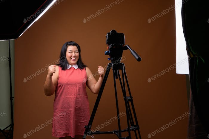 Overweight Asian woman vlogging in studio with dslr camera on tripod