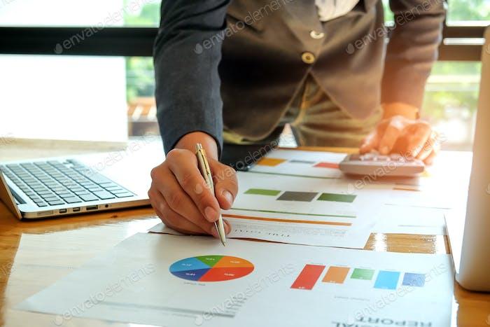 Geschäftsmann mit Taschenrechner analysiert einen Graphen.