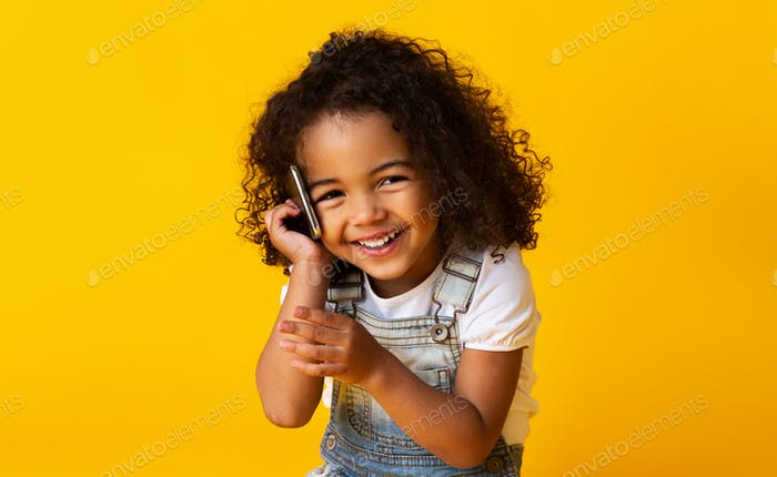 Cute afro girl talking on cellphone on yellow background