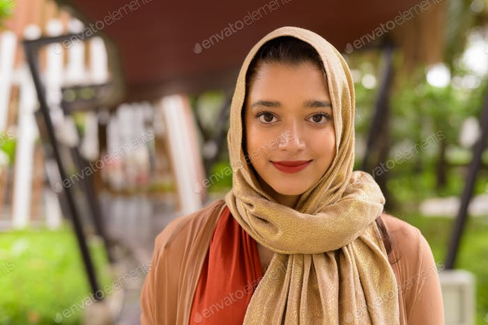 Face of young beautiful Indian Muslim woman in the city with nature