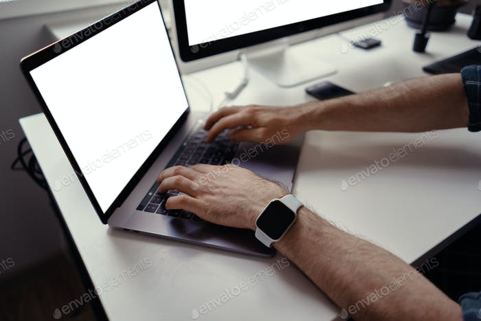 Man hands working on laptop with white screen at home