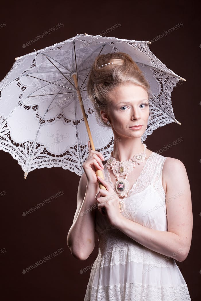 Beautiful woman in vintage dress holding a lace umbrella