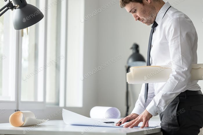 Businessman or arhitect in white shirt using ruler and pencil wh