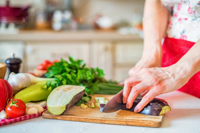 Close up female hand with knife cuts eggplant on wooden board in kitchen. Cooking vegetables