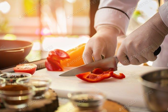 Knife cuts red paprika