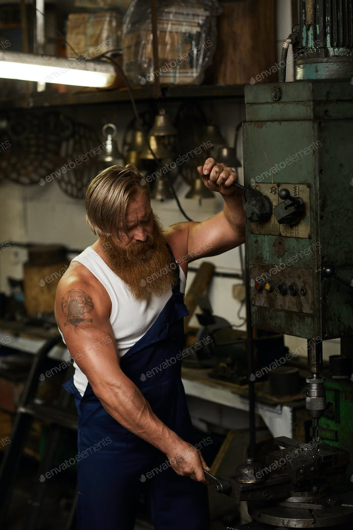 Muscular craftsman working with drilling machine